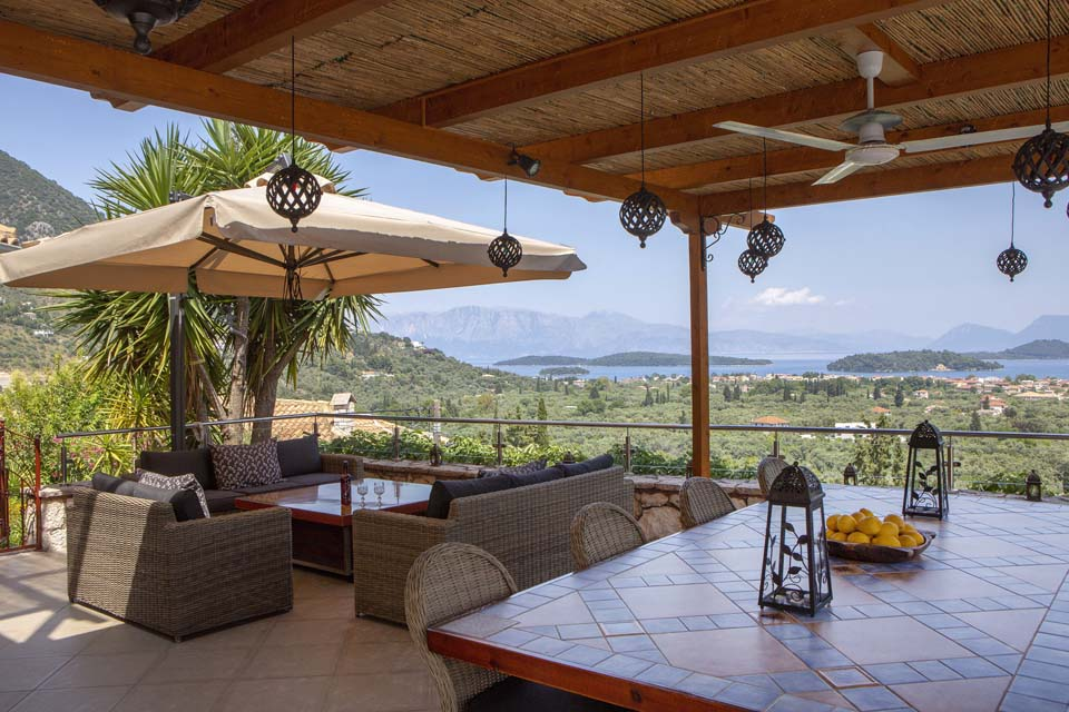 Outdoor dining table and fire table overlooking Ionian Islands to mainland Greece
