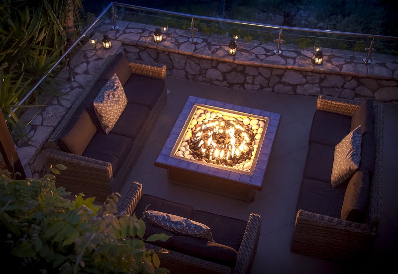 Outdoor lounging area with fire table at Villa Octavius